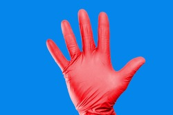 Hand stop gesture. Red latex glove isolated. Five fingers palm open hand. Higiene virus protection background.