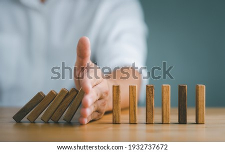 Hand Stopping the domino business crisis effect or risk protection concept, business solution and intervention Stockfoto ©