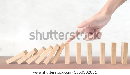 Hand stopping the Domino effect stopped by unique.business idea #1550332031