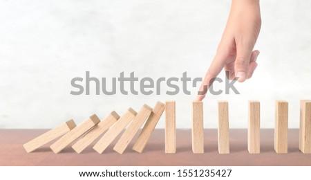 Hand stopping the Domino effect stopped by unique.business idea #1551235427