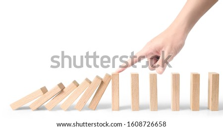 Hand stopping the Domino effect stopped by unique.business idea