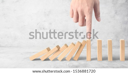 Hand stopping the Domino effect stopped by unique, Business Ideas #1536881720