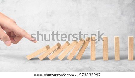 Hand stopping the Domino effect stopped by unique, Business Ideas #1573833997