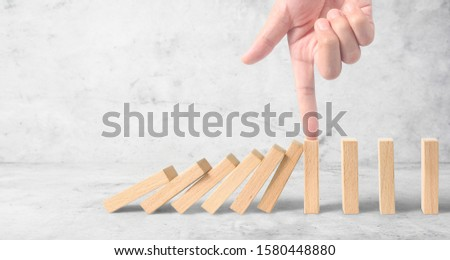 Hand stopping the Domino effect stopped by unique, Business Ideas #1580448880