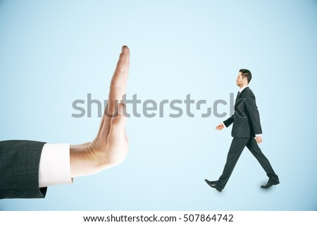 Hand stopping walking sman miniature on blue background