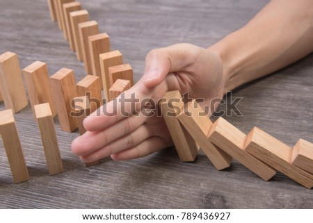 hand stopping wooden block domino. concept prevent and solution. #789436927