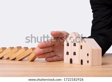 Hand stopping wooden block domino with home. concept home insurance.