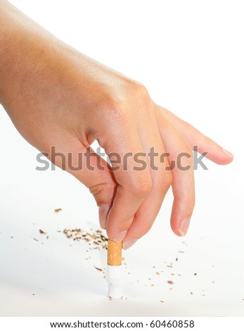 Hand stubbing out a cigarette on white surface isolated