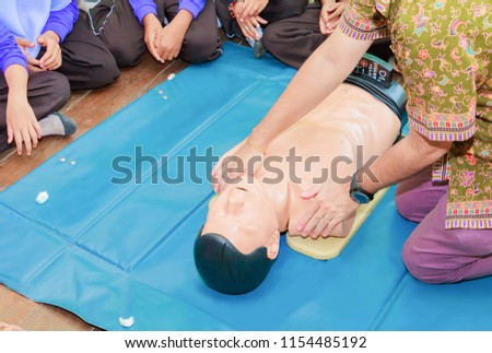 hand student Heart pump with medical dummy on CPR, in emergency refresher training to assist of physician #1154485192