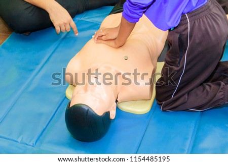 hand student Heart pump with medical dummy on CPR, in emergency refresher training to assist of physician #1154485195