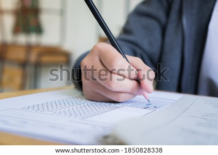 Hand Student use pencil writing on paper optical form of standardized test examination, Answer sheet,doing final exam attending in examination classroom Stok fotoğraf ©