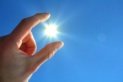 hand sun and blue sky with copyspace for text message