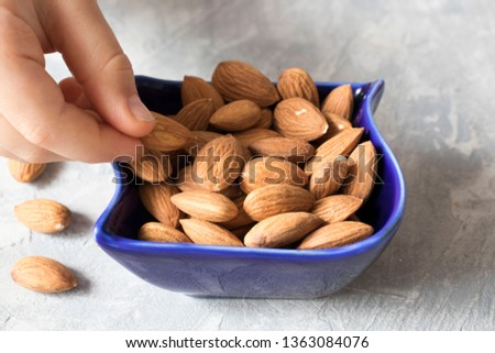 hand takes almonds in a blue bowl on the table, healthy food concept