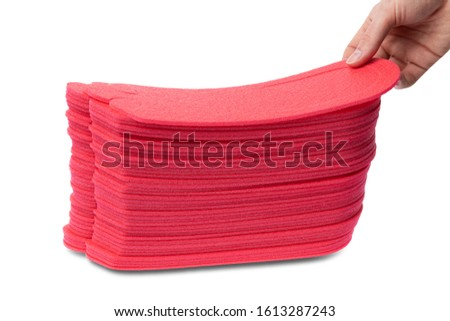 hand takes one Red Disposable Slippers. a hand takes one foam rubber sneaker
