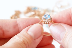 hand takes ring with big blue topaz and white diamonds around on other jewerly background, jewerly inspect and verify, pawnshop concept