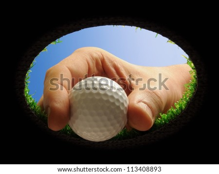 hand taking a golf ball out of a golf hole seen from below