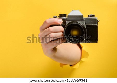 Hand taking a picture with a camera through torn yellow paper background. Paparazzi everywhere concept.