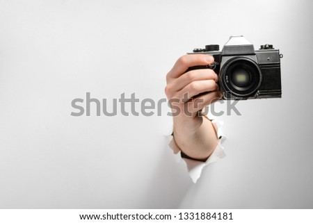 Hand taking a shot with a camera through torn white paper background. Annoying paparazzi concept.
