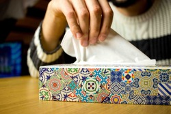 Hand taking a tissue from a tissues box. Concept of illness and cold. When the flu is coming