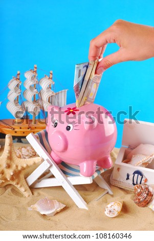 hand taking  money out from pink piggy bank standing on the beach