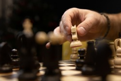 Hand taking next step on chess game. Human hand moving wooden white knight piece on Chess board selective focus. Blurred black pieces in foreground. Chess pieces in style of minimalist abstract design