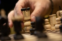 Hand taking next step on chess game. Human hand moving wooden white queen piece on Chess board selective focus. unexpected winning business solution concept. Chess pieces minimalist abstract design