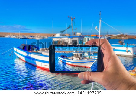 Hand taking picture with a smartphone of a fishing boat in the harbor in summer