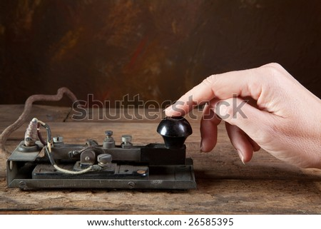 Hand tapping morse code on an antique telegraph