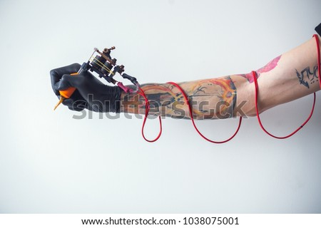 hand tattoo artist with the tattoo machine on a white background. the red wires #1038075001