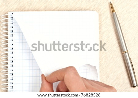 Hand tearing one paper page from notepad on desk