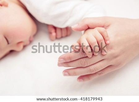 Hand the sleeping baby in the hand of mother close up, New family and baby protection from mom concept