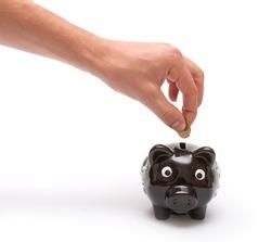 Hand thorows coin in piggy moneybox