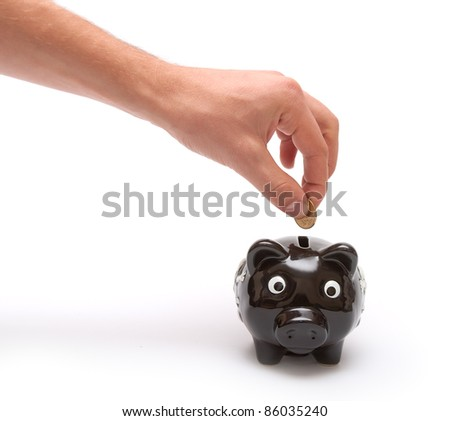Hand thorows coin in piggy moneybox
