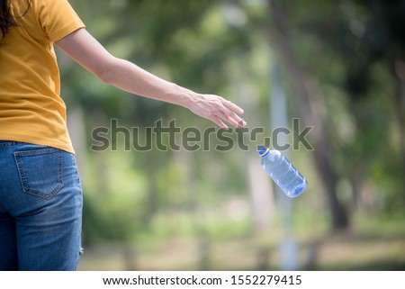 Hand throwing away plastic bottle in nature. Environmental damage by plastic waste.Environmental conservation Stockfoto ©