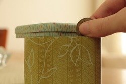 Hand throwing money into green patterned box. Be thrifty. Save money.
