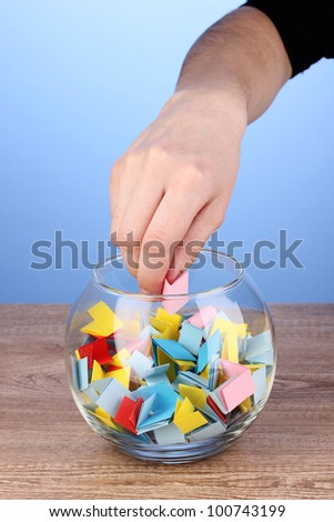 Hand throwing piece of paper for lottery on wooden table on blue background