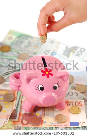 hand  throwing the coin into pink piggy bank standing on banknotes background