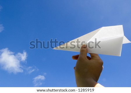 Hand throwing the paper airplane to the air