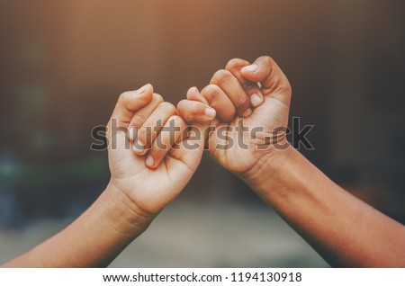 Hand to pinky swear,Happy couple or friendship holding hands together forever love concept.