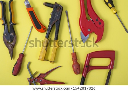 Hand tools on a yellow background.