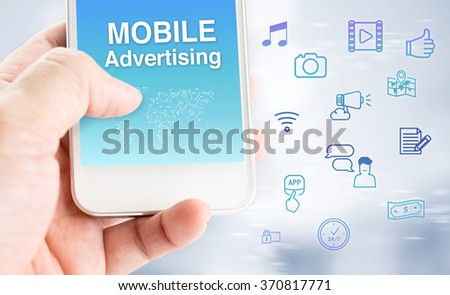 Hand touch mobile phone with mobile advertising word with feature icon at blurred grey background, Digital marketing business concept