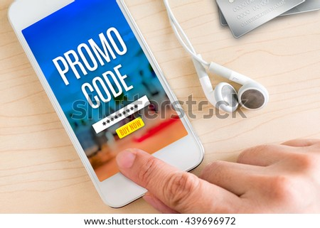 Hand touch smart phone and ear phone with Promo code word on wood table ,Internet marketing concept.