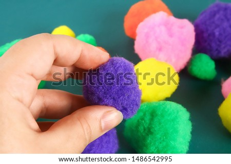 Hand touches a soft woolen pompom. The concept of touch, tactility, feelings.