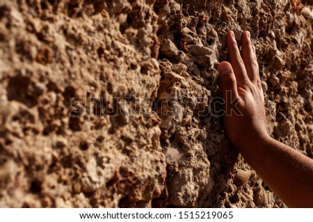 Hand touches an antique limestone wall close-up. Touch of antiquity