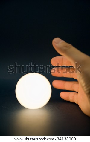 Hand touching a bright ball, Concept of magic