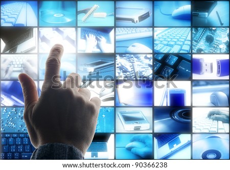 hand touching a wall of panels with technology images
