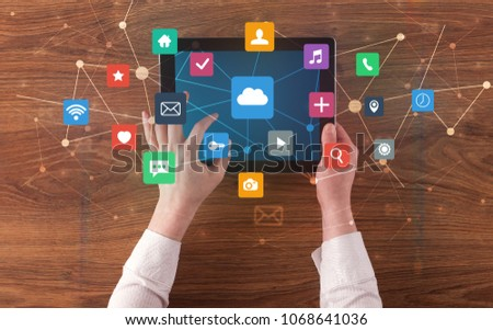 Hand touching multitask tablet with cloud wifi message social media call icons and symbols concept - Shutterstock ID 1068641036