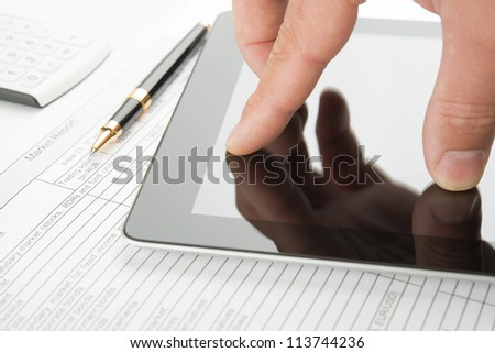 Hand touching screen of contemporary digital tablet computer