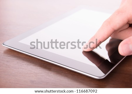 hand touching screen on modern digital tablet pc. Close up