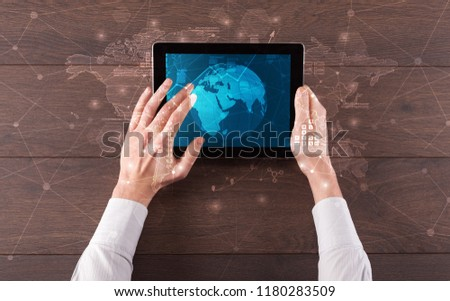 Hand touching tablet with worldwide reports links and statistics concept #1180283509